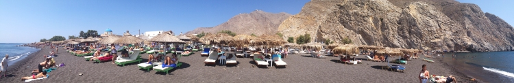 Perissa black sand beach on Santorini (the site of Ancient Thira lies atop that mountain)