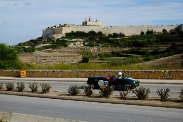 A vintage car races past Mdina during the Grand Prix